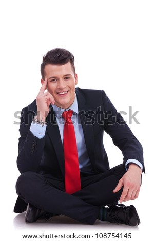 cool fashion business man sitting on white background and looking at the camera