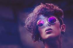 Cool fashion model girl in round mirror sunglasses smoking cigarette.Fashionable young woman smokes cig outdoor.Trendy hairstyle,lip piering,sharp cheekbones and beautiful pink lips.Close up portrait