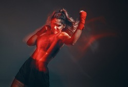 Cool female fighter in boxing bandages trains in studio in red neon light. Mixed martial arts. Long exposure shot
