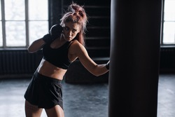 cool female fighter in boxing gloves trains in the gym. Mixed martial arts