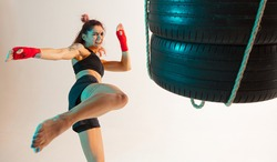 Cool female fighter trains kicking with punching bag made of tires in neon studio light. Women's sport workout