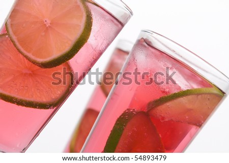 Cool, fresh, red cocktail with lime on a white background