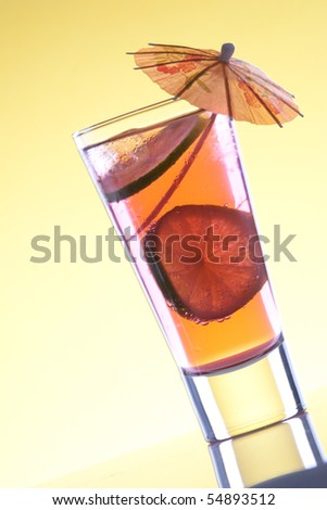 Cool, fresh, red cocktail with lime on a yellow background