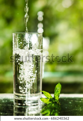 Cool fresh water with ice and mint. Splash in glass. Healthy life concept