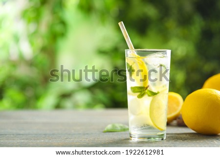 Cool freshly made lemonade and fruits on grey wooden table. Space for text