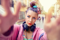 Cool funky young rebel girl with headphones and crazy hair enjoy power of music taking selfie on street – hipster woman with trendy avant-garde look having fun - Music fan concept with carefree teen
