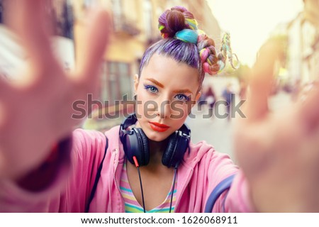 Cool funky young rebel girl with headphones and crazy hair enjoy power of music taking selfie on street – hipster woman with trendy avant-garde look having fun - Music fan concept with carefree teen Stock photo ©