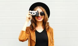 Cool funny girl model with retro film camera wearing a elegant hat, brown jacket, curly hair outdoors over city grey background