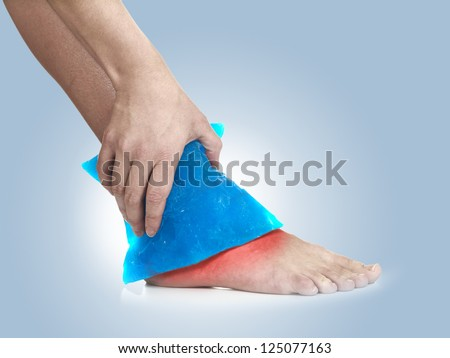 Cool gel pack on a swollen hurting ankle. Medical concept photo.  Color Enhanced skin with read spot indicating location of the pain.
