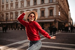 Cool girl in red sweater looks away. Attractive short-haired woman in beige hat and sunglasses walks outdoors.