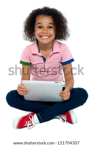 Cool girl kid sitting on the floor with wide grin on face holding tablet pc.