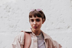 Cool girl with short hair looking into camera on background on white backdrop. Brunette lady with glass in beige outside posing on backdrop of wall..