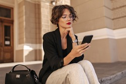 Cool girl with wavy hair in white trousers and balck jacket holding phone outside. Stylish woman in eyeyglases sitting outdoors..