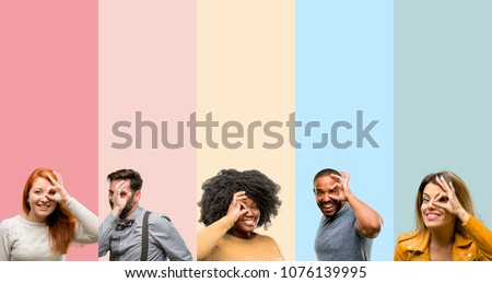 Cool group of people, woman and man looking at camera through fingers in ok gesture. Imitating binoculars, beautiful eyes and smile