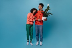 Cool guy and his girlfriend posing with plans on blue background. Young happy woman in orange sweater and brunette man in jeans hug