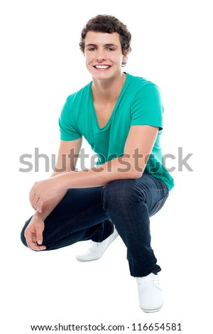 Cool guy wearing white sneakers, squatting posture. Looking at camera