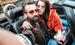 Cool happy couple taking selfie at roadster car trip - Bearded man with beautiful woman having fun on roadtrip experience - Luxury concept with people traveling together - Focus on face of hipster guy