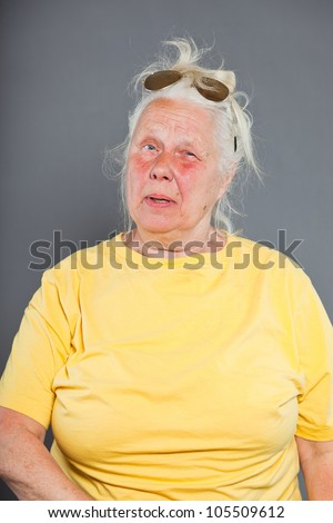 Cool hip senior woman with sunglasses and long grey hair. Expressive face. Studio shot isolated on grey.