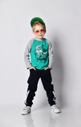 Cool impish frolic blond kid boy buddy in cap, sunglasses grey sweatshirt with dinosaur print, black sport pants with stripes and white sneakers stands holding hands in his pockets