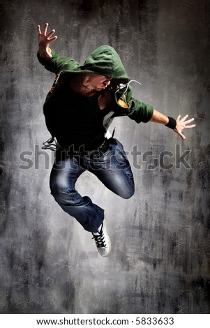 cool looking dancer posing on a grunge grey wall