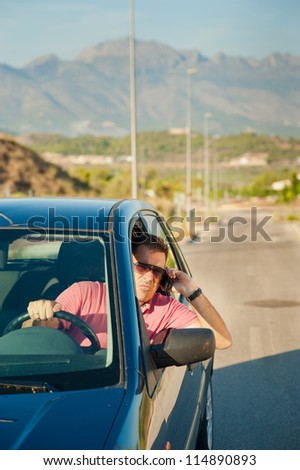 Cool looking guy using is phone while driving