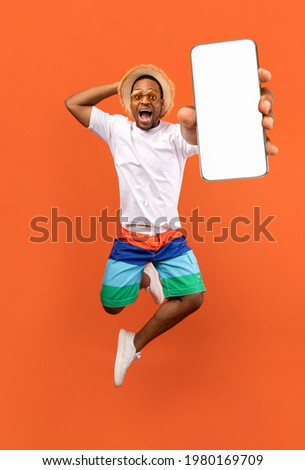 Cool mobile offer. Excited jumping black guy demonstrating smartphone with white screen on orange studio background, collage with mockup copy space for app or website design Foto stock ©