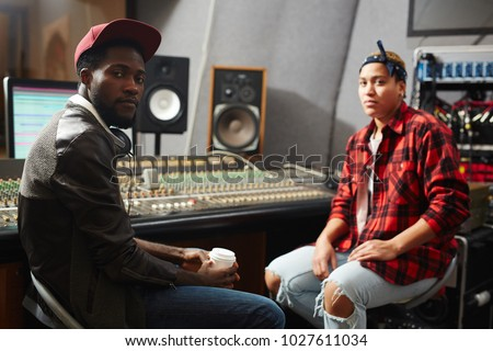 Cool musician with headphones looking at camera in studio of recording with sound operator on background