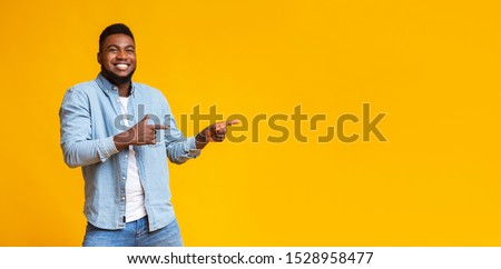 Cool offer. Cheerful african american man pointing two fingers aside at copy space on yellow studio background, panorama