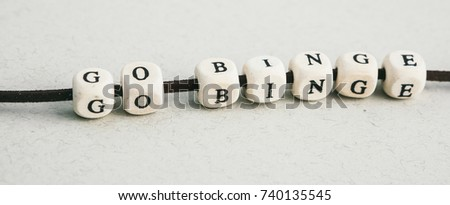 Cool phrase Go Binge made of wooden beads on lather lace. A series of minimalistic conceptual compositions of beads on gray background. Words, phrases and expressions. Horizontal long format banner #740135545