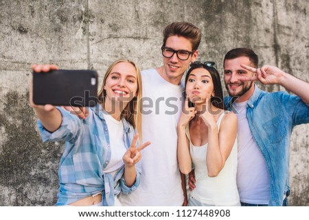 Cool picture of company standing together on grey background. Blonde girl is taking selfie of her company. She is smiling and showing piece symbol. Her friends are also posing but in a funny way. #1127448908