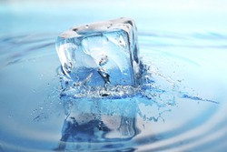 cool refreshing ice-cube dropped into freshly poured water. splashes frozen in time.
