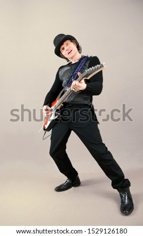 Cool rock guitarist in a hat playing the electric guitar on a gray backdrop. Musician performing in a studio.