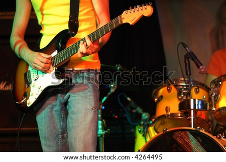 Cool rocker playing guitar in  a rock concert