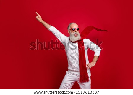 Cool santa character aged man directing finger on advert banner wear sun specs knitted clothes isolated red background