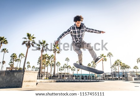 Cool skateboarder outdoors - Afroamerican guy jumping with his skate and performing a trick #1157455111