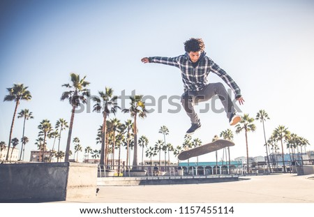 Cool skateboarder outdoors - Afroamerican guy jumping with his skate and performing a trick #1157455114