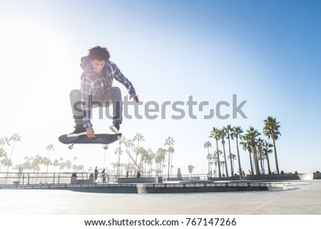 Cool skateboarder outdoors - Afroamerican guy jumping with his skate and performing a trick #767147266