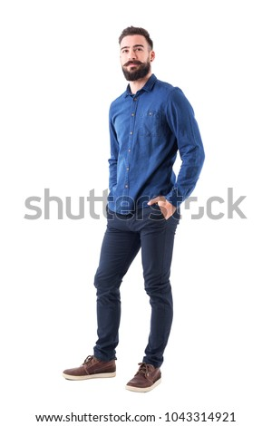 Cool smiling guy, with hands in pockets looking up wearing blue denim shirt and pants. Full body isolated on white background. #1043314921