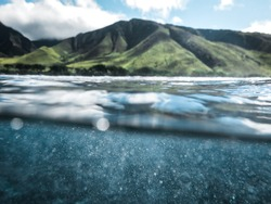 Cool Split Photo Half Underwater with Clear Blue Ocean Water Drops and Lush Green Mountain Background with Sunshine on Clear Beautiful Day in Tropical Island Paradise on Maui Hawaii