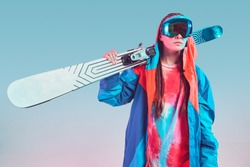 Cool sporty young female skier in stylish colorful winter sportswear with ski posing in studio in neon light