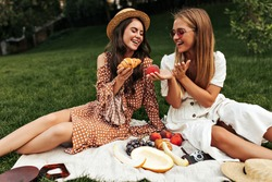 Cool tanned girls in midi summer dresses have picnic outside. Brunette girl in boater smiles and holds croissant. Cheerful lady in red sunglasses holds fresh apple.