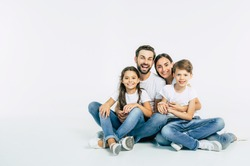 Cool team. Beautiful and happy smiling young family in white T-shirts are hugging and have a fun time together while sitting on the floor and looking on camera.