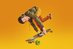 Cool teen boy rides and does tricks on a skateboard. Youth active lifestyle. Yellow background.