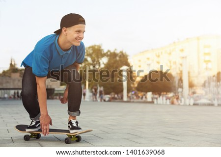 Cool Teen Skater Riding On Skateboard in Urban Area, Summer Evening, empty space