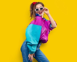 Cool teenager. Fashionable DJ girl in colorful trendy jacket and vintage retro sunglasses enjoys style of 80s - 90s vibes. Teenager Girl at disco party. Young fashion model on yellow color background.