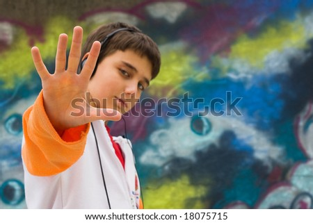 Cool teenager with his hand up, against a graffiti wall