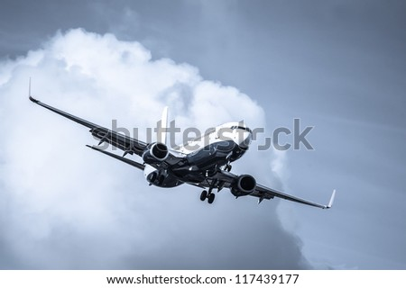 cool toned passenger jet on landing approach through a cloudy sky