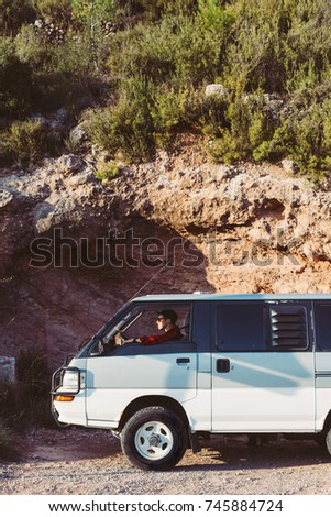 Cool trendy middle aged man tourist embarks on adventure to travel around roads less ridden, he sits on driver sits behind wheel of vintage retro camping van  #745884724