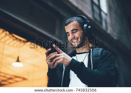 Cool trendy young millennial from generation z laughs and smiles on camera, walks outside with smartphone and big wireless headphones, enjoys new technology and immersive reality