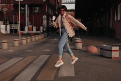 Cool woman in beige jacket jumping at street. Girl with short hair in jeans, glasses and light sneakers with backpack and cup of tea posing outside..